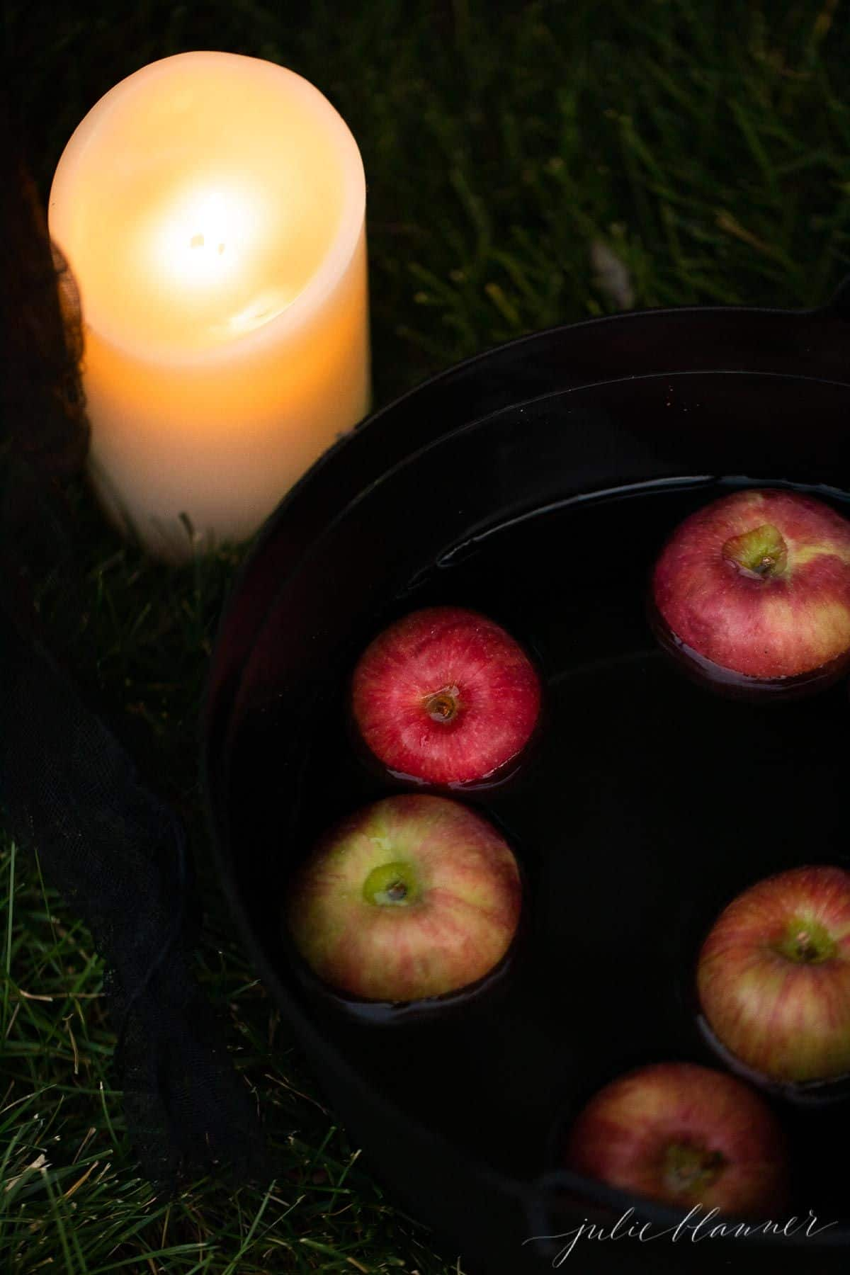 A cauldron full of fresh apples and a battery powered pillar candle sitting in grass.