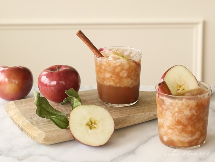 Clear glasses filled with an old fashioned with apples and cinnamon, fresh apples nearby.