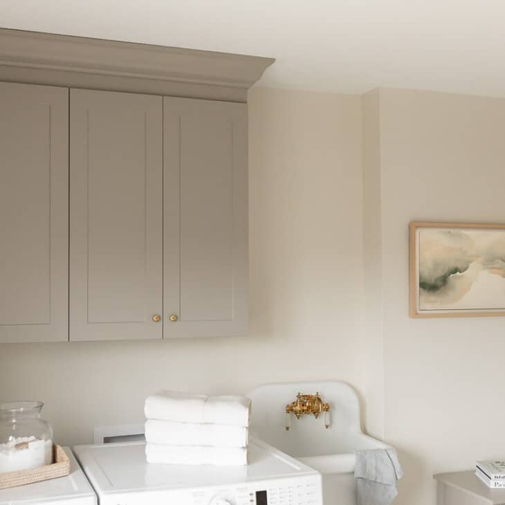 A laundry room with gray full overlay cabinets above the washer and dryer.