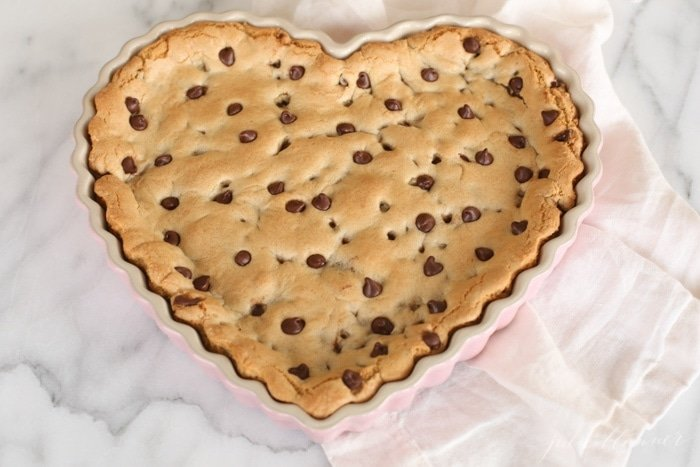 cookie cake with chocolate chips in a heart shaped tart pan