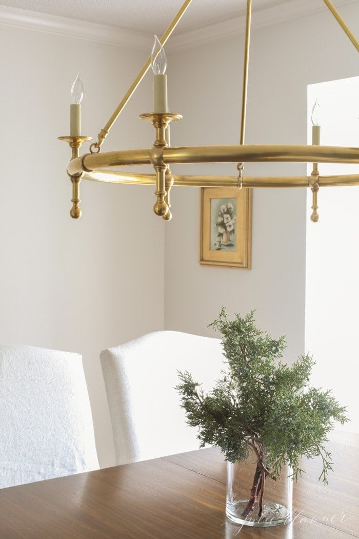 A brass chandelier over fresh greens for winter decor in a dining room.