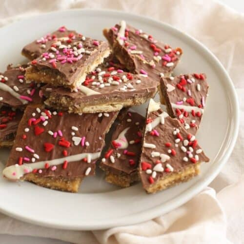 Easy toffee made with saltines, decorated with valentine's sprinkles on a white plate.