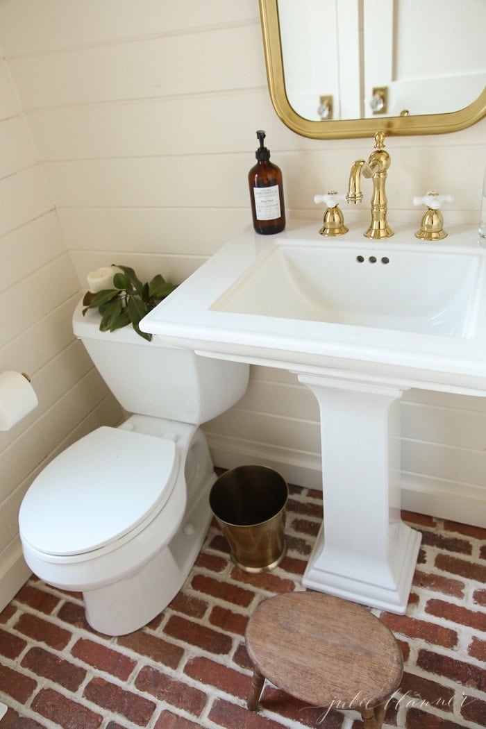 A white bathroom with brick floors, magnolia placed on toilet tank for a little winter decor.