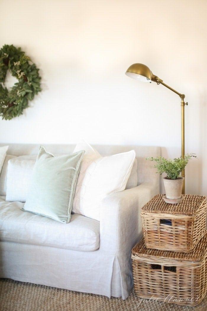 Winter decor of an evergreen wreath hung over a linen couch.