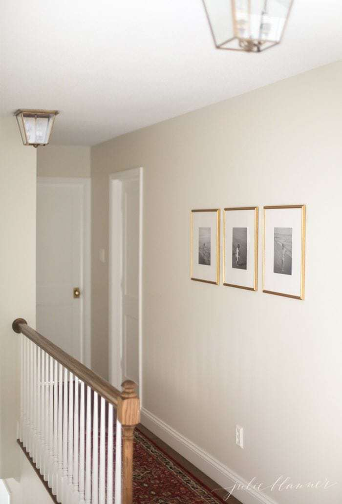beautiful hall with brass lanterns and diy wall art of three framed photos.