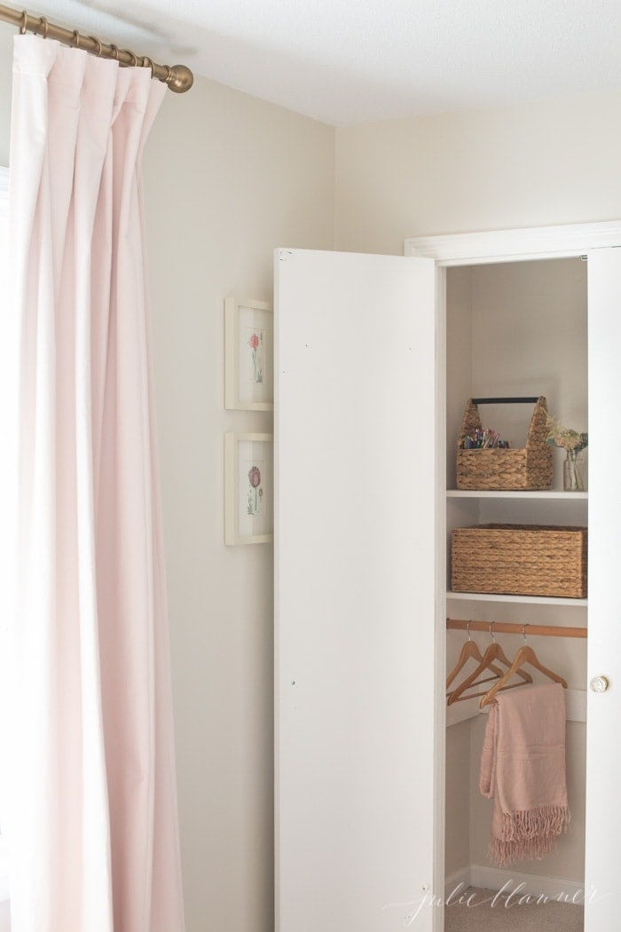 Looking inside a kids bedroom closet organization with basket storage.