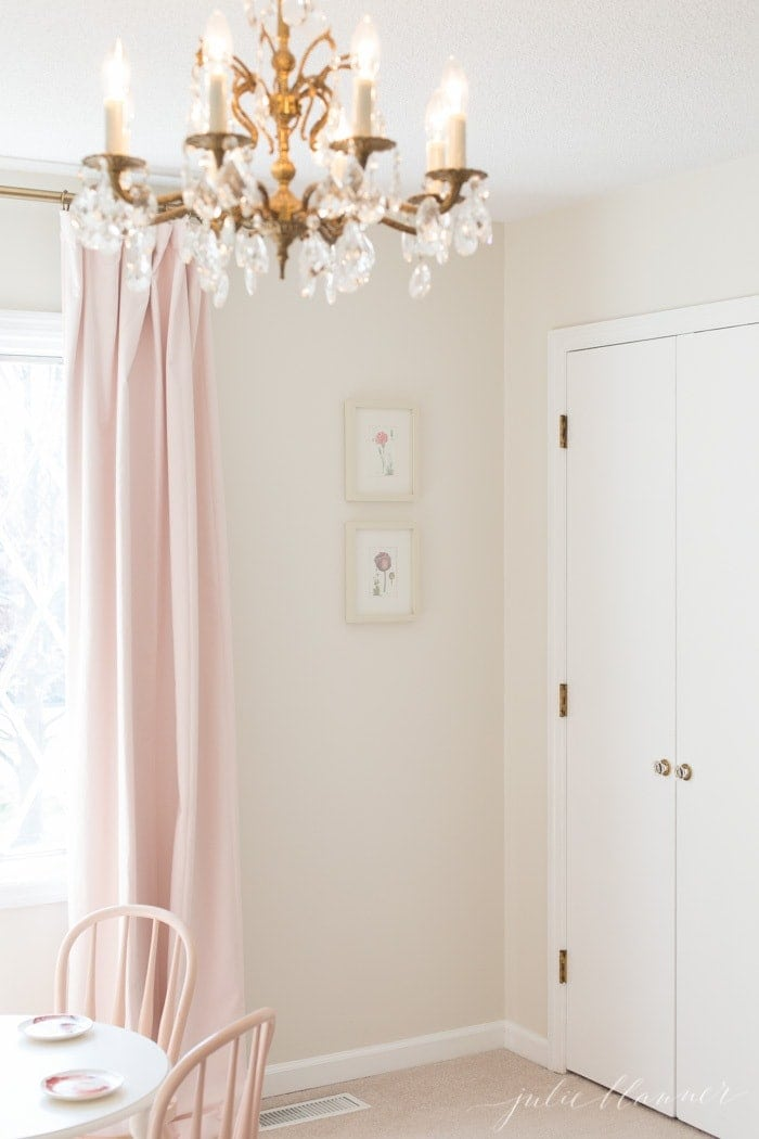 A white kids bedroom with a vintage chandelier, pink curtains and floral wall art.