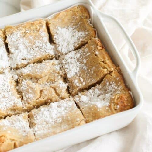 A white baking dish full of sliced gooey butter cake without a cake mix.