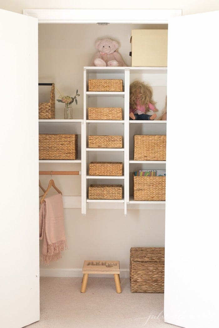 Looking inside a kids closet organization with basket storage.