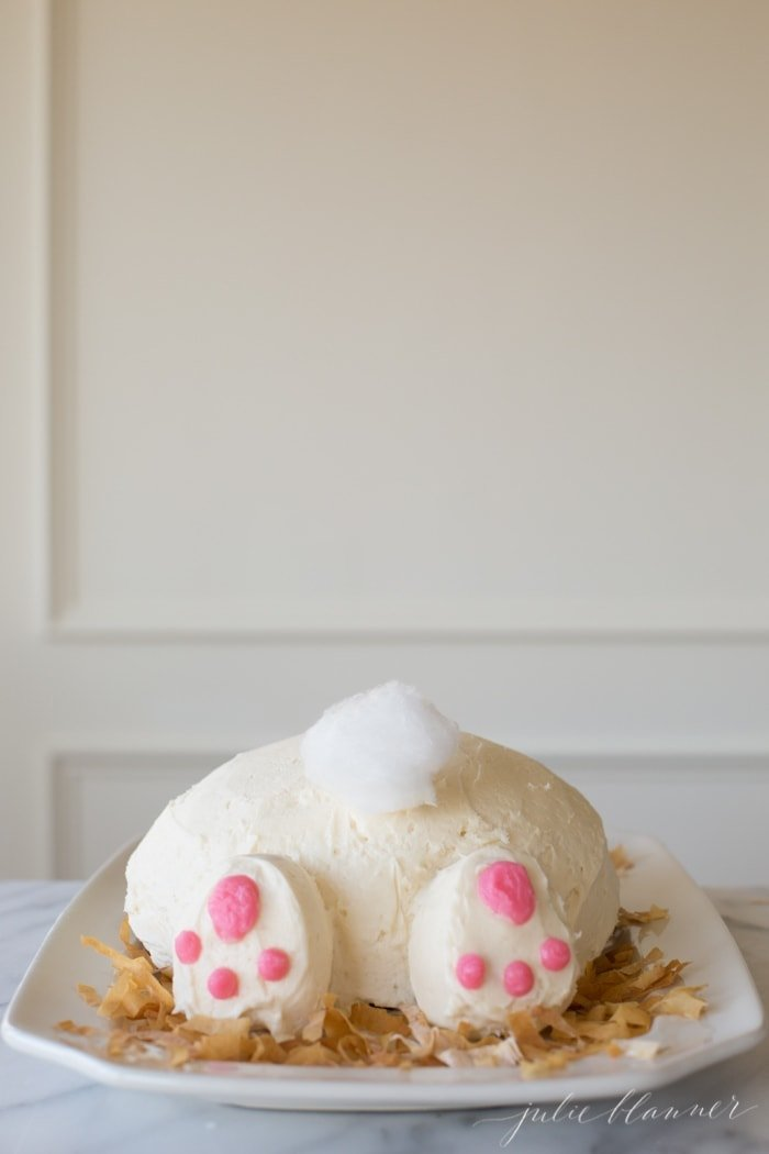 A vintage inspired bunny cake with a bunny tail made of cotton candy on a white platter.