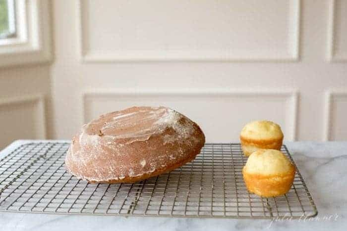 A round cake and two small cupcakes on a cooling rack on a marble surface.