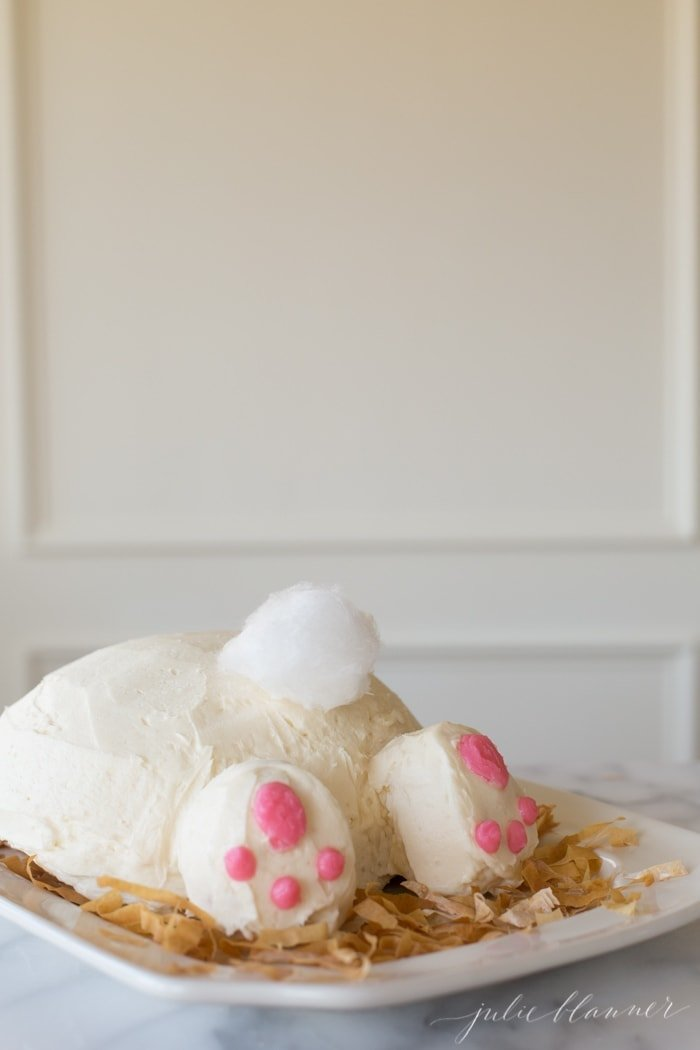A bunny butt cake on a white platter, tail made of white cotton candy