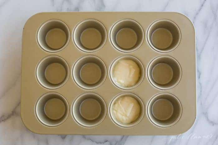 A gold muffin tin with two muffin spaces filled with cake mix.