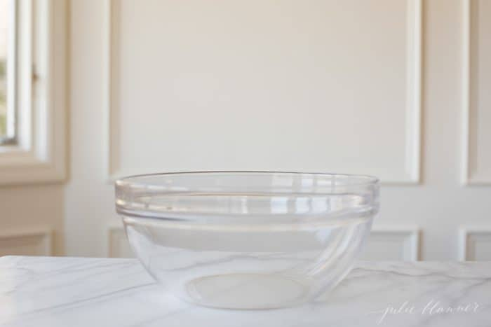 A clear glass pyrex mixing bowl on a marble surface.