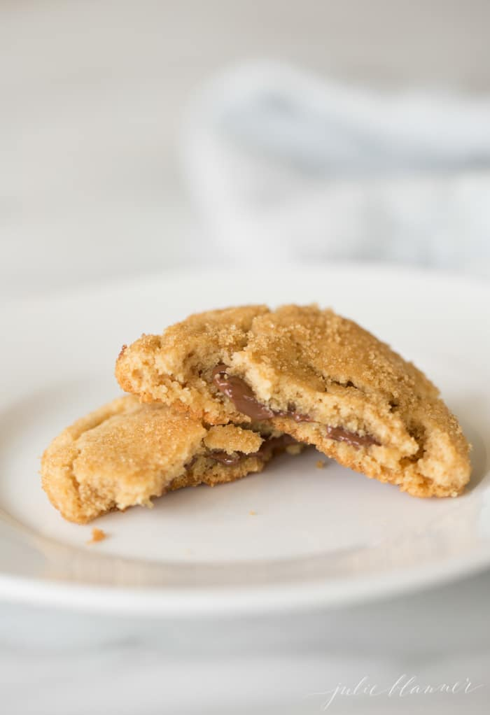 Peanut butter cookie broken in half with melted chocolate dripping out on a white plate