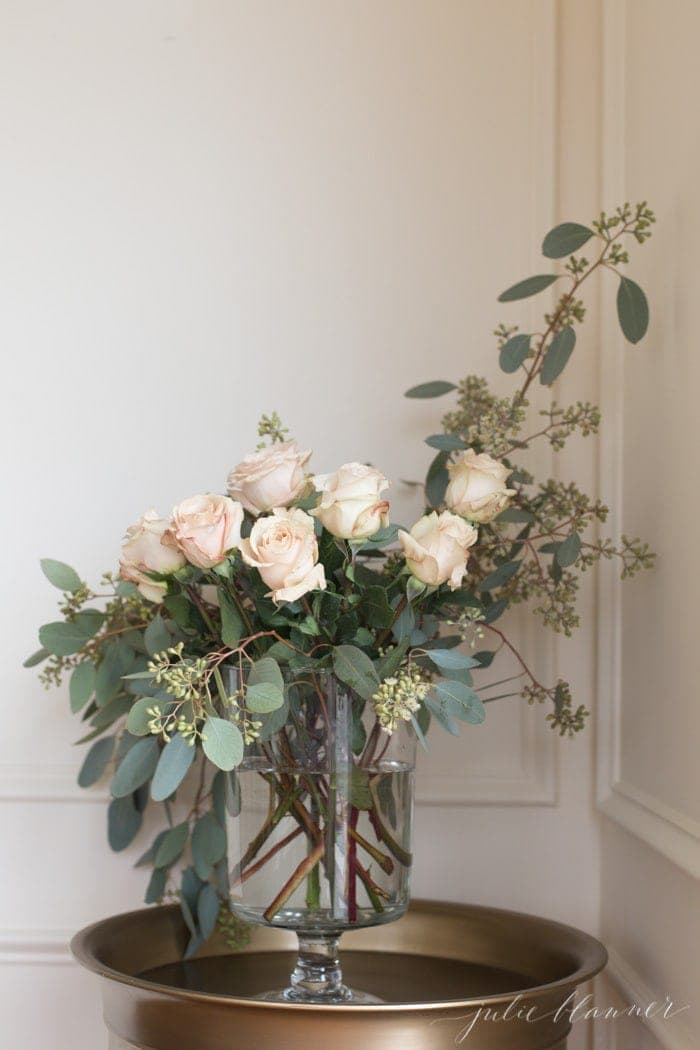 A vase of roses and eucalyptus against a white wall