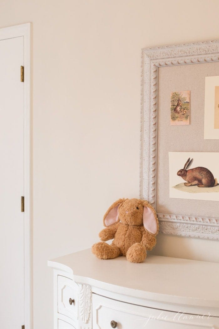 A girl's dresser in a white bedroom, Easter decorating ideas on the pinboard.