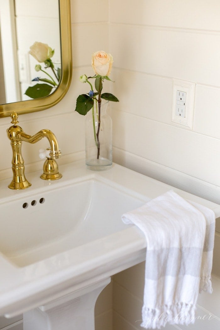 A white bathroom with shiplap walls and pedestal sink.
