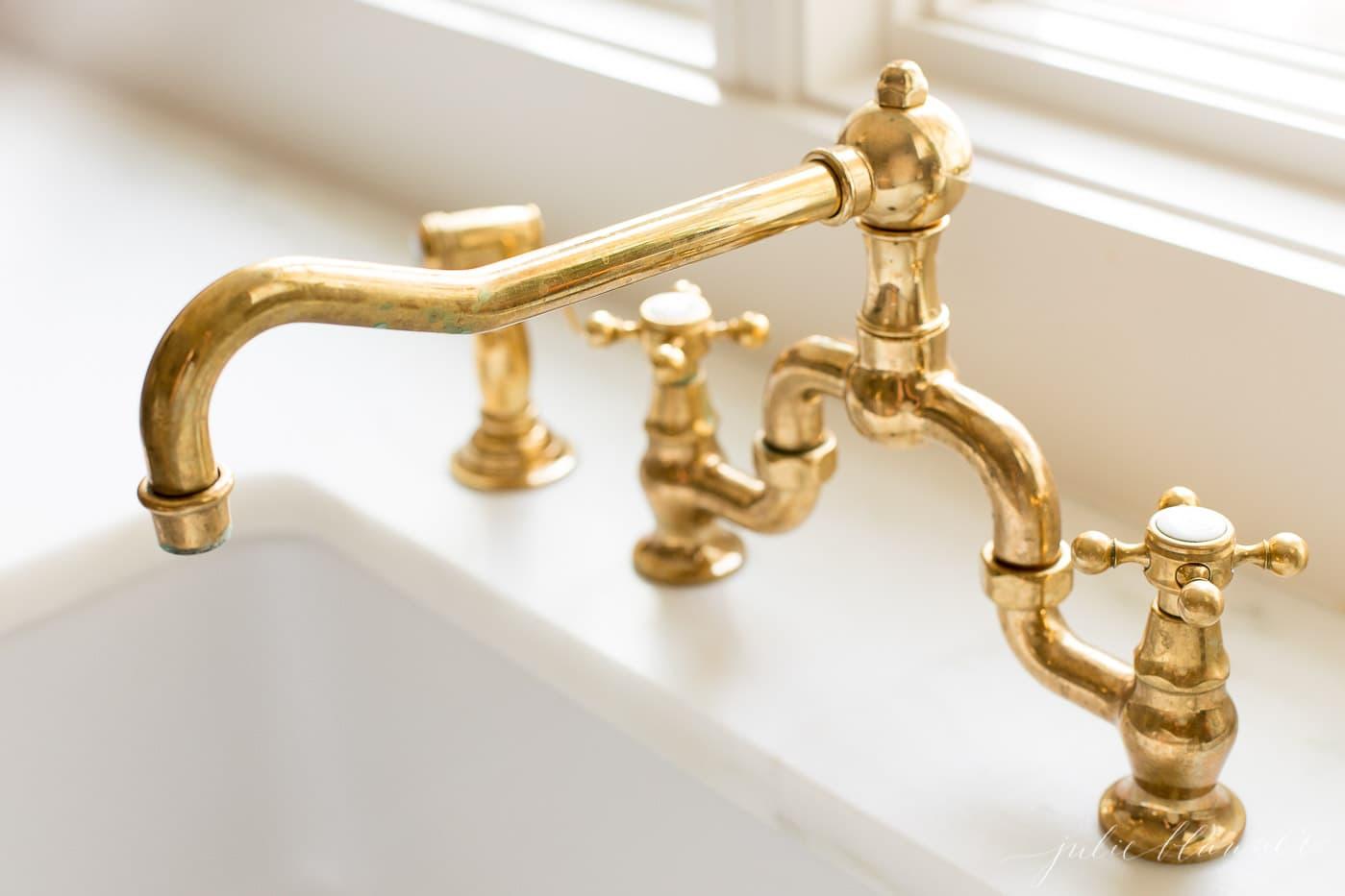 A brass bridge faucet over a farmhouse sink.