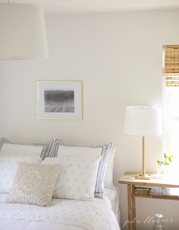 Looking inside a white bedroom with a black and white photo on the wall over the bed.
