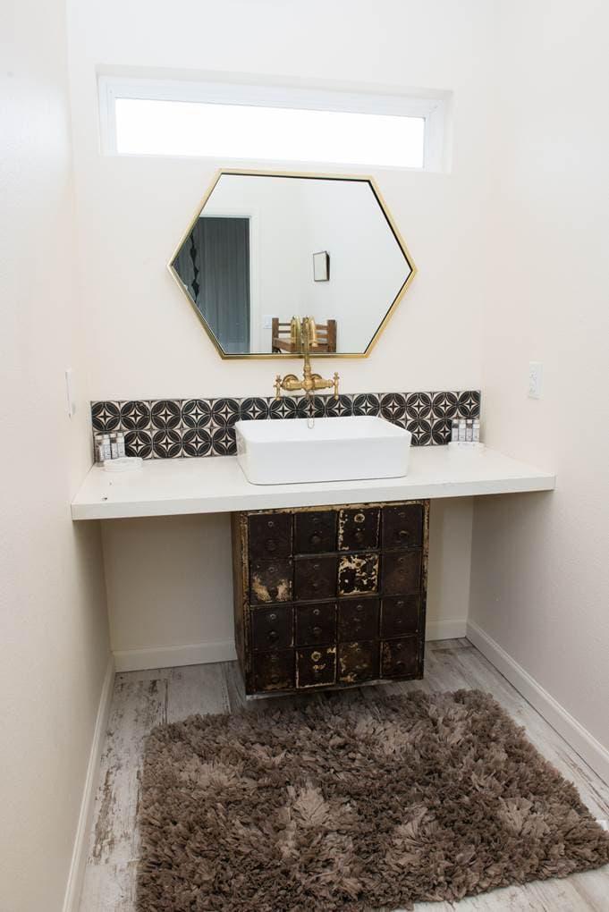 A modern industrial farmhouse bathroom with a raised sink and geometric brass mirror.