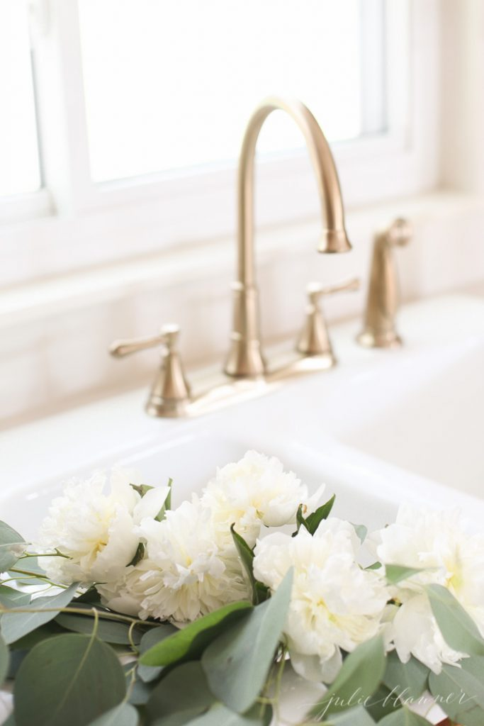 champagne bronze faucet and flowers in an original porcelain sink