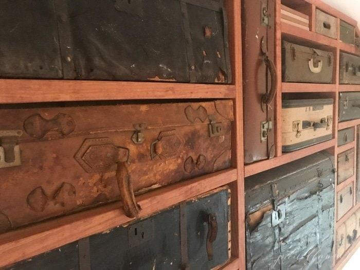 A vintage suitcase display case between wooden beams.