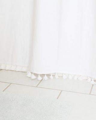 easy bathroom updates - tassel shower curtain and crock waste basket