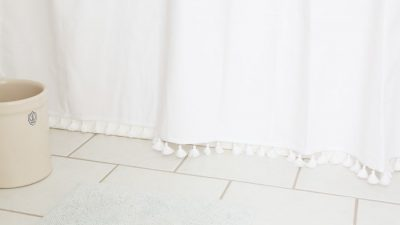easy bathroom updates - tassel shower curtain and crock waste basket