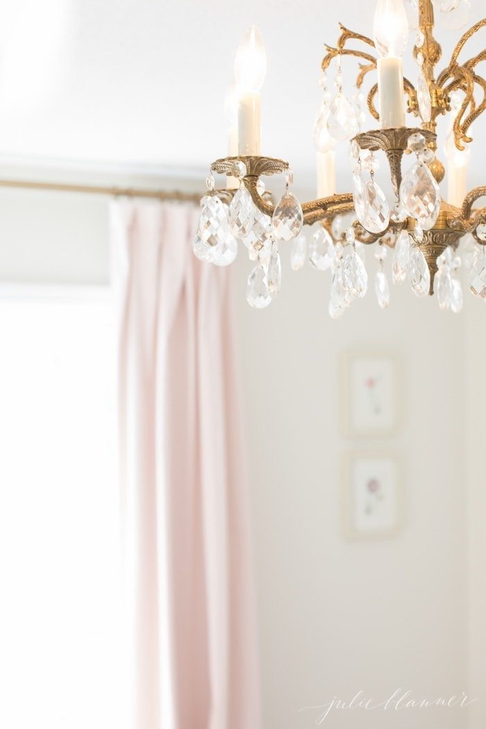 Pale pink curtains in the background of a white bedroom, vintage gold chandelier in focus of image.