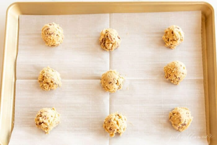 A gold baking sheet lined with parchment paper and round scoops of pecan pie cookie recipe dough.