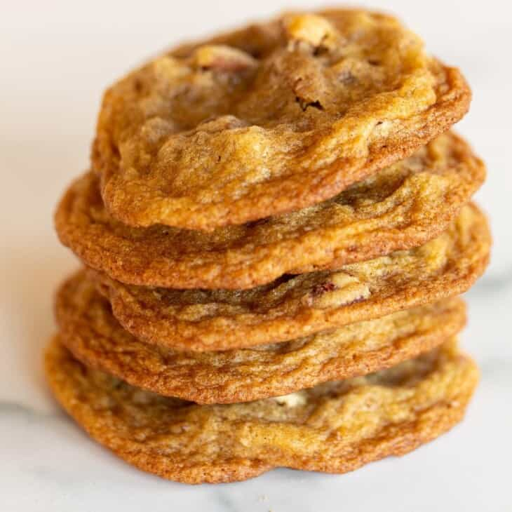 A stack of thin pecan pie cookies on a marble surface.