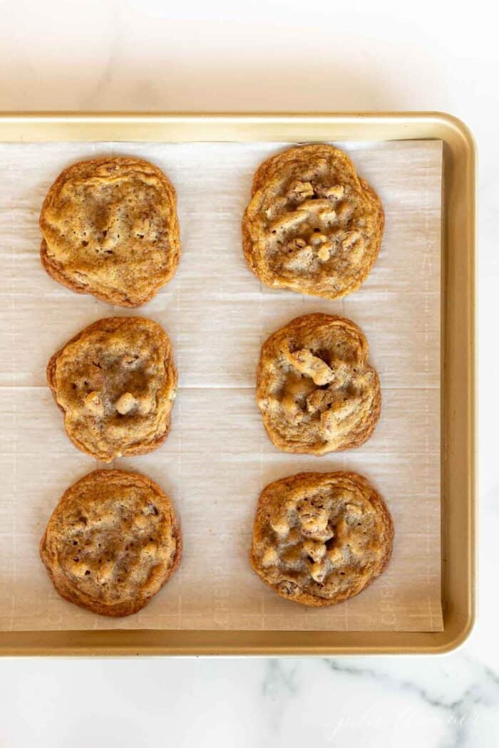 A gold baking sheet lined with parchment paper and six pecan pie cookies.