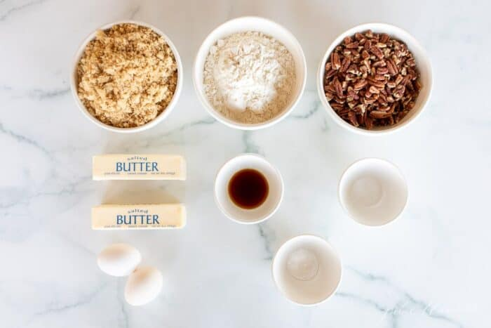 A marble surface with ingredients for butter pecan pie cookies laid out in small white bowls.