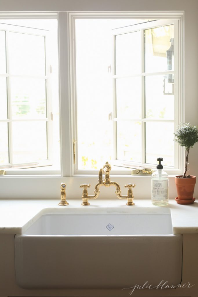 myrtle topiaries flanking a farmhouse sink and brass faucet