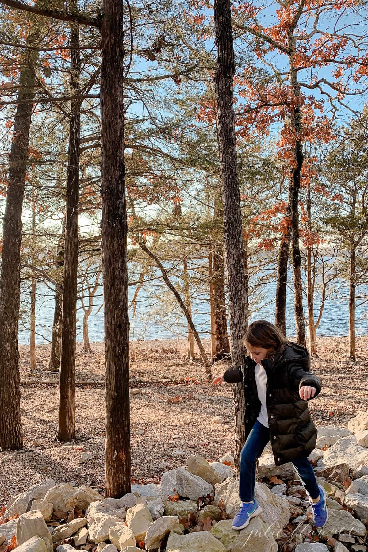 A little girl hiking in the woods on a list of free things to do in branson mo