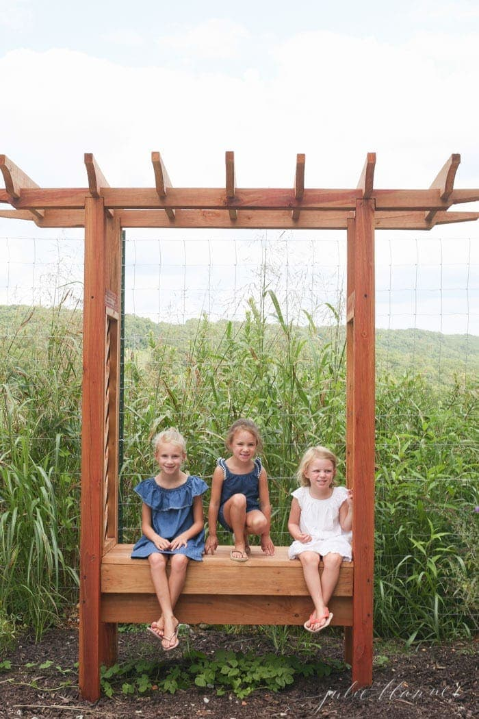 Three little girls sitting on a garden bench with grasses behind them.