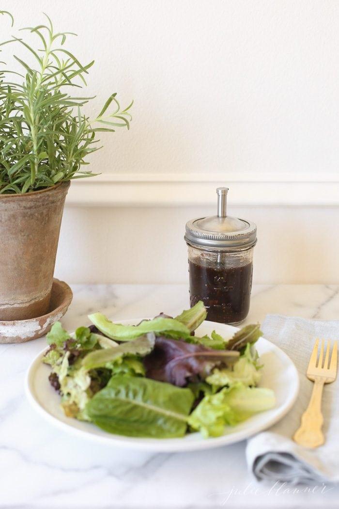 balsamic vinaigrette next to a plate of mixed greens
