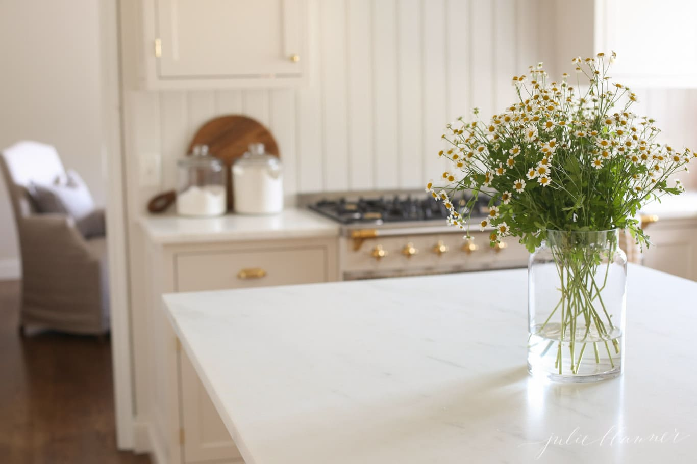 A cream kitchen with marble countertops and a vase of flowers on the island.