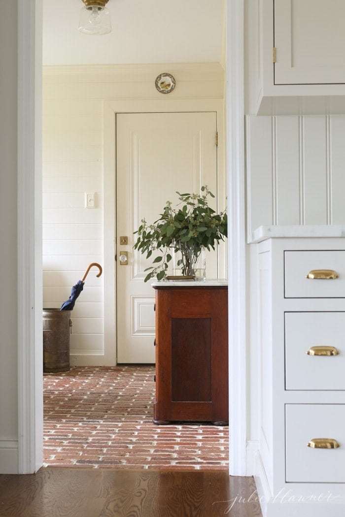 mudroom with brick floor and cream shiplap walls decorated for fall