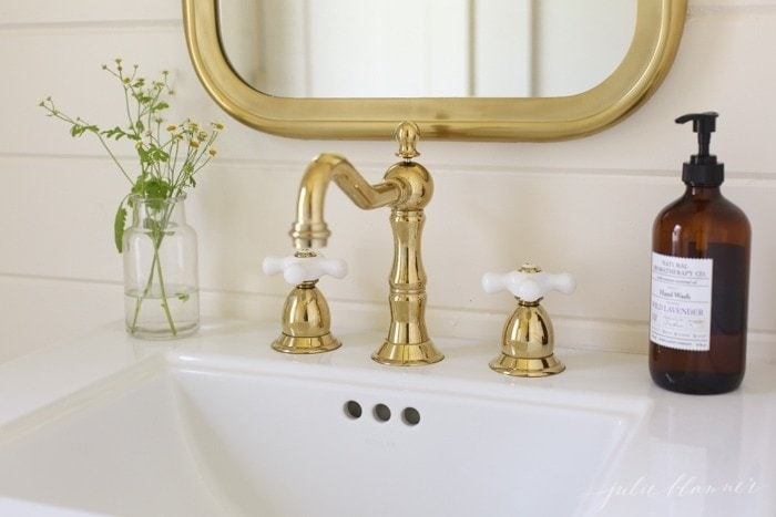 A white pedestal sink with a brass bathroom faucet and a vase of flowers nearby
