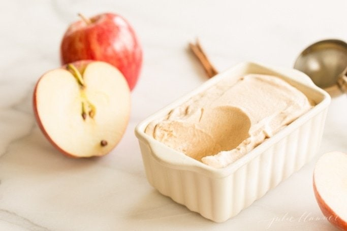 Apple butter ice cream in a small ceramic loaf dish, sliced apples surrounding.