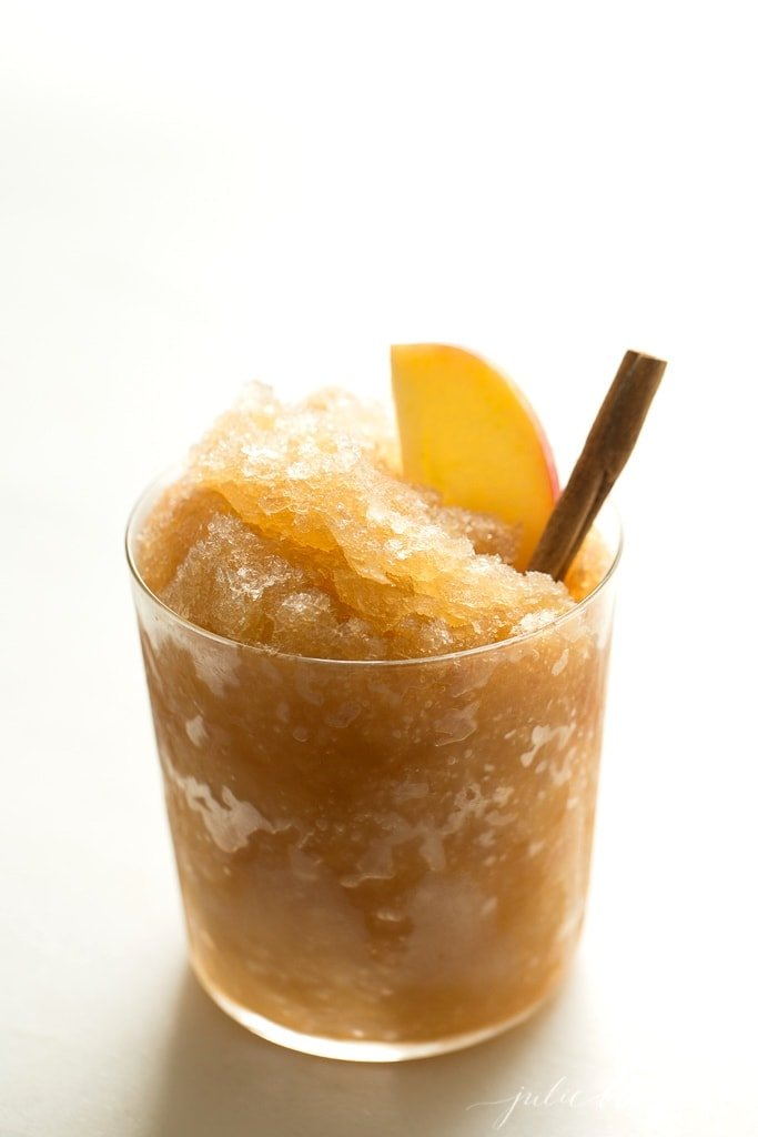apple cider slushy recipe in clear glass vases, garnished with cinnamon stick and apple slices