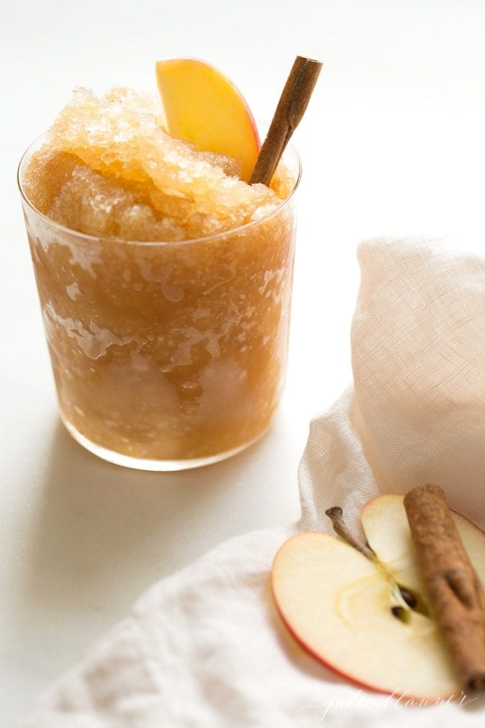 apple cider slush garnished with apple slice and cinnamon stick
