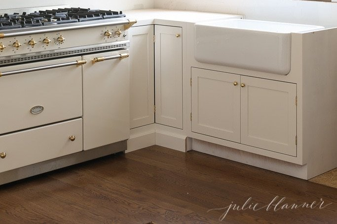 classic apron front sink in porcelain in a remodeled kitchen with cream cabinets.