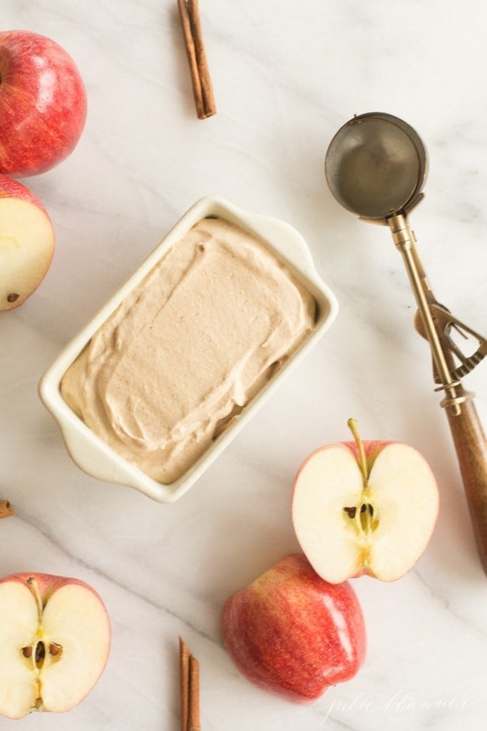 A marble surface with sliced apples, cinnamon sticks and a container of homemade apple ice cream.