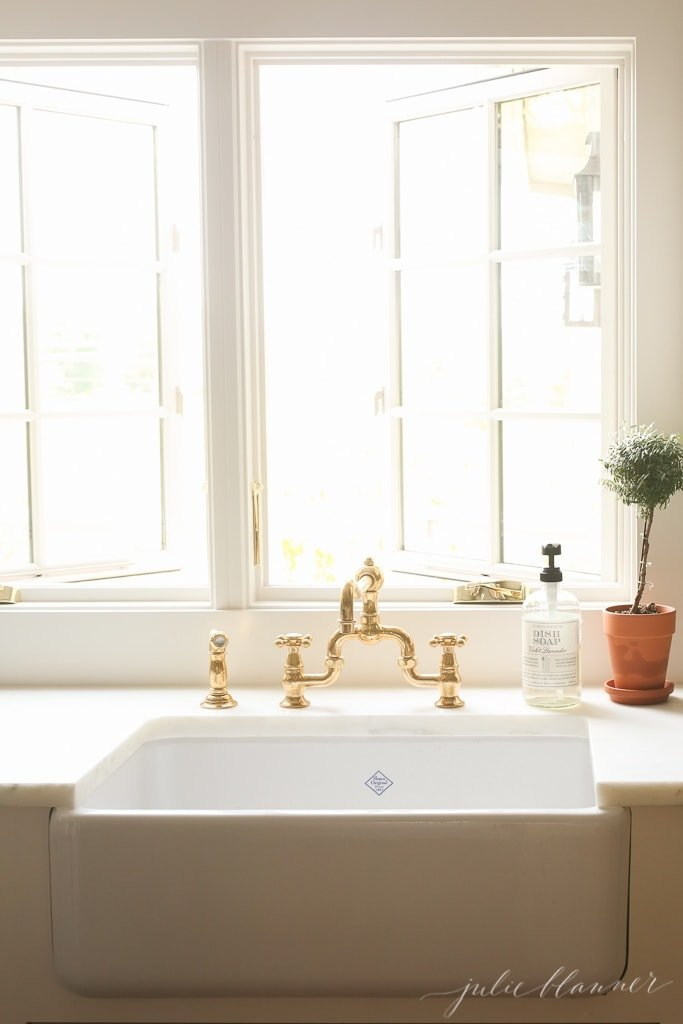 A white kitchen sink in a white kitchen, windows open above.