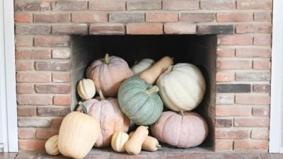 pretty fall decorating idea heirloom pumpkins spilling out of fireplace