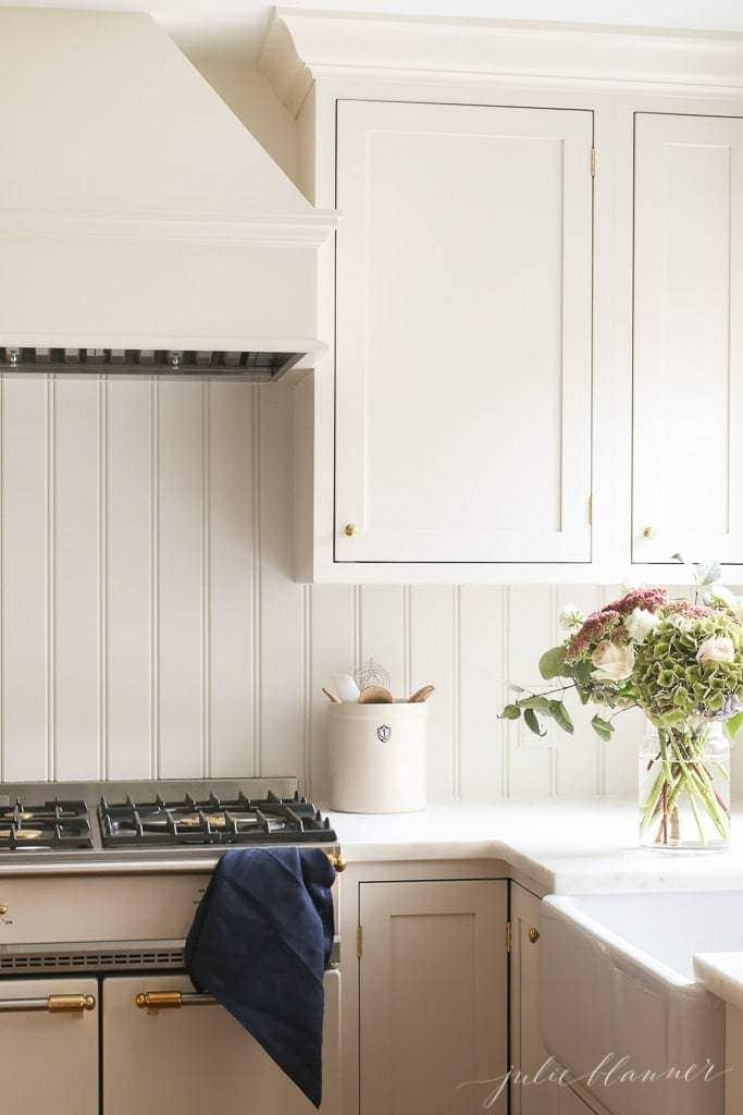 an apron front sink in a cream kitchen, vase of flowers to the side.