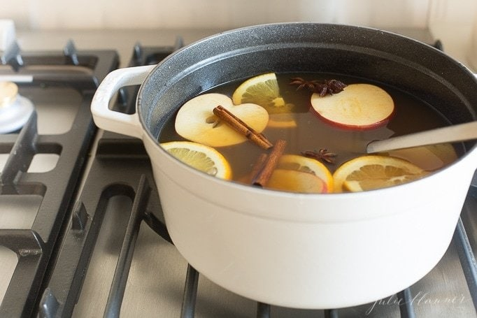 warm bourbon apple cider in a white pot on the stovetop